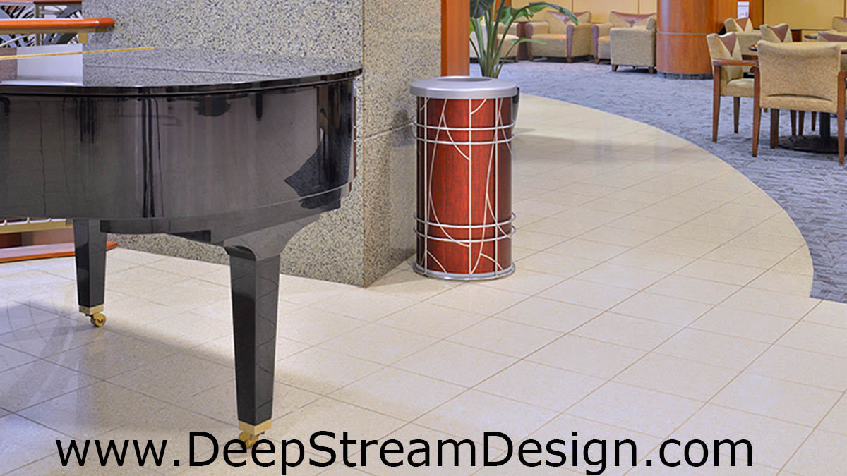 "DeepStream Designs' Modern Chameleon Trash Bin with Tree aluminum graphics inside a stainless steel frame with adjustable feet housing a leak proof removable recycled plastic liner with a 9"" Kydex lid"